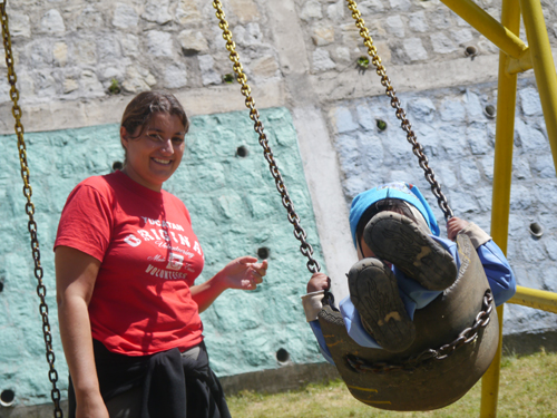 Tam pushing kids on a swing in Ecuador