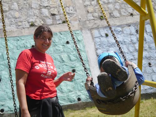 Tam pushing kids on a swing in Ecuador