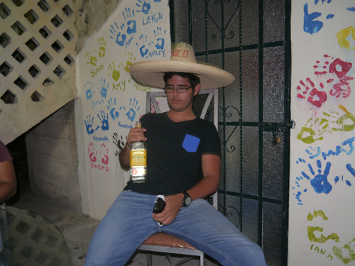 Mexican man holding Tequila in a sombrero
