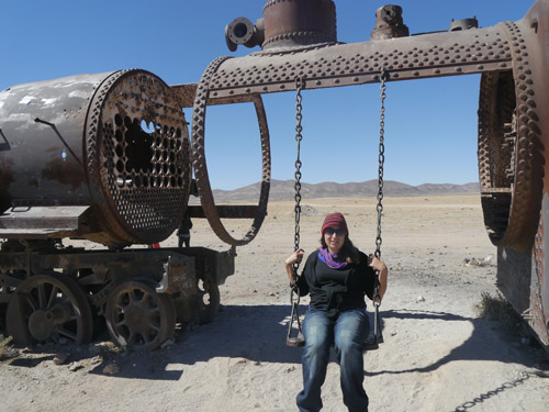 Tam on a swing in the train graveyard, Bolivia